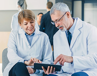 Doctors sitting together looking at tablet and pointing at it.